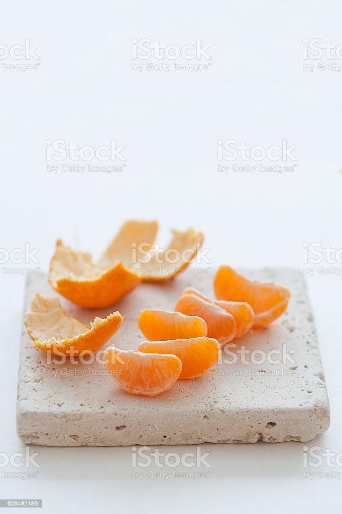 Mandarin oranges wedges on natural stone board royalty-free stock photo