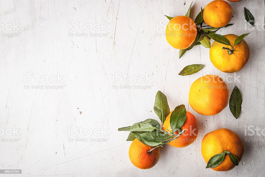 Mandarins at the right on the white wooden table horizontal stock photo