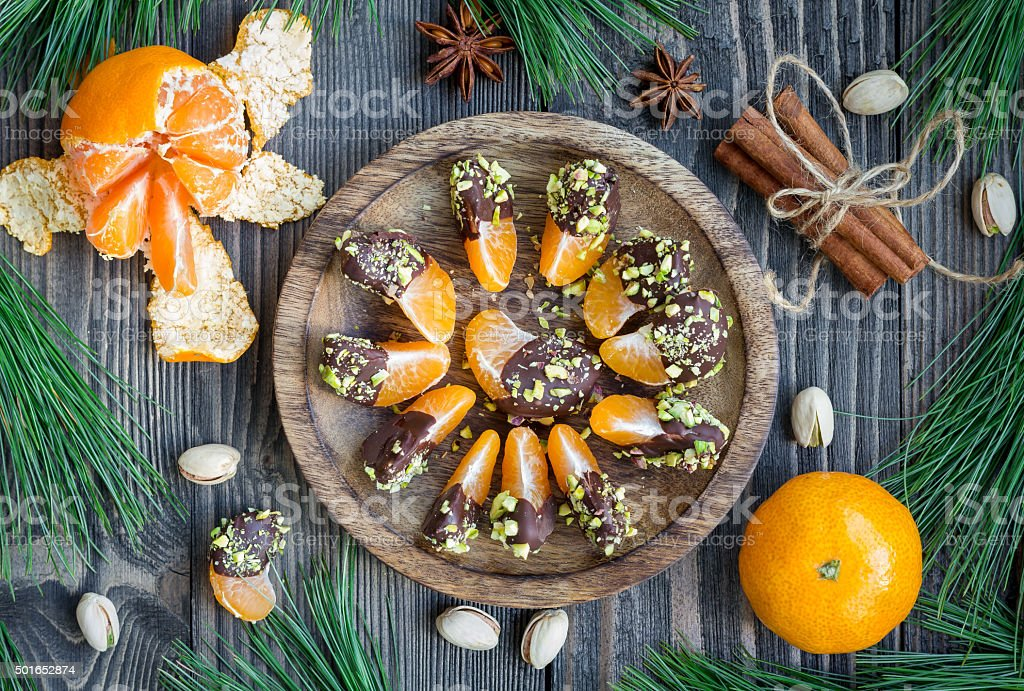 Mandarins covered with chocolate and pistachio, top view stock photo
