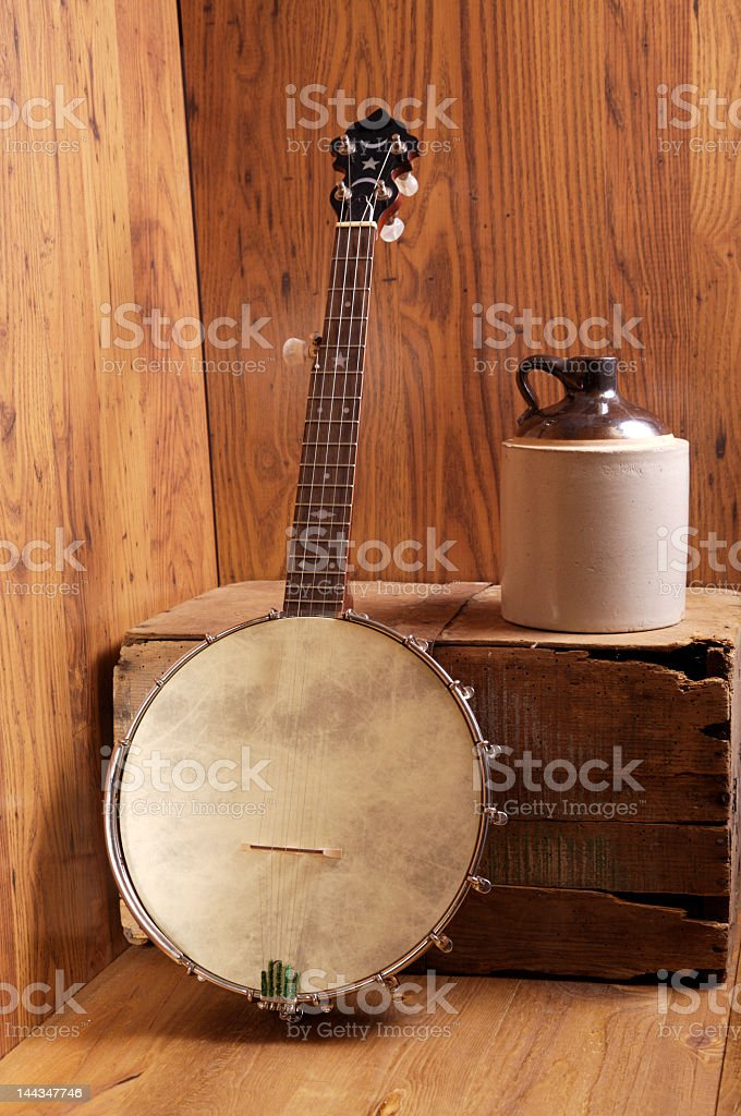 Mandolin resting on wooden box next to jug on wooden shed stock photo