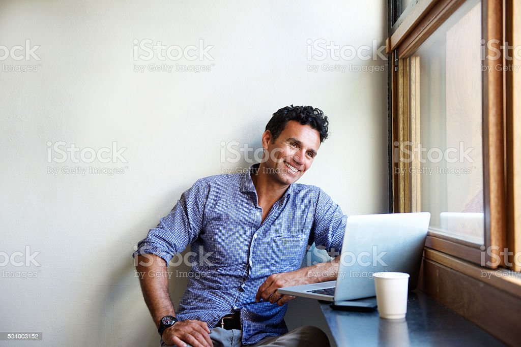 Mandsome modern man smiling with laptop at cafe stock photo