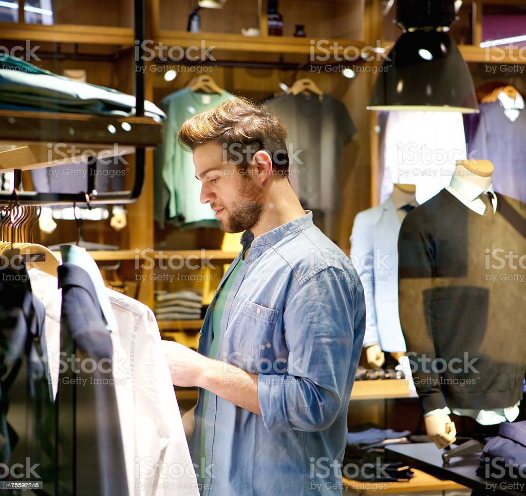 Mandsome young man shopping for clothes at shop stock photo
