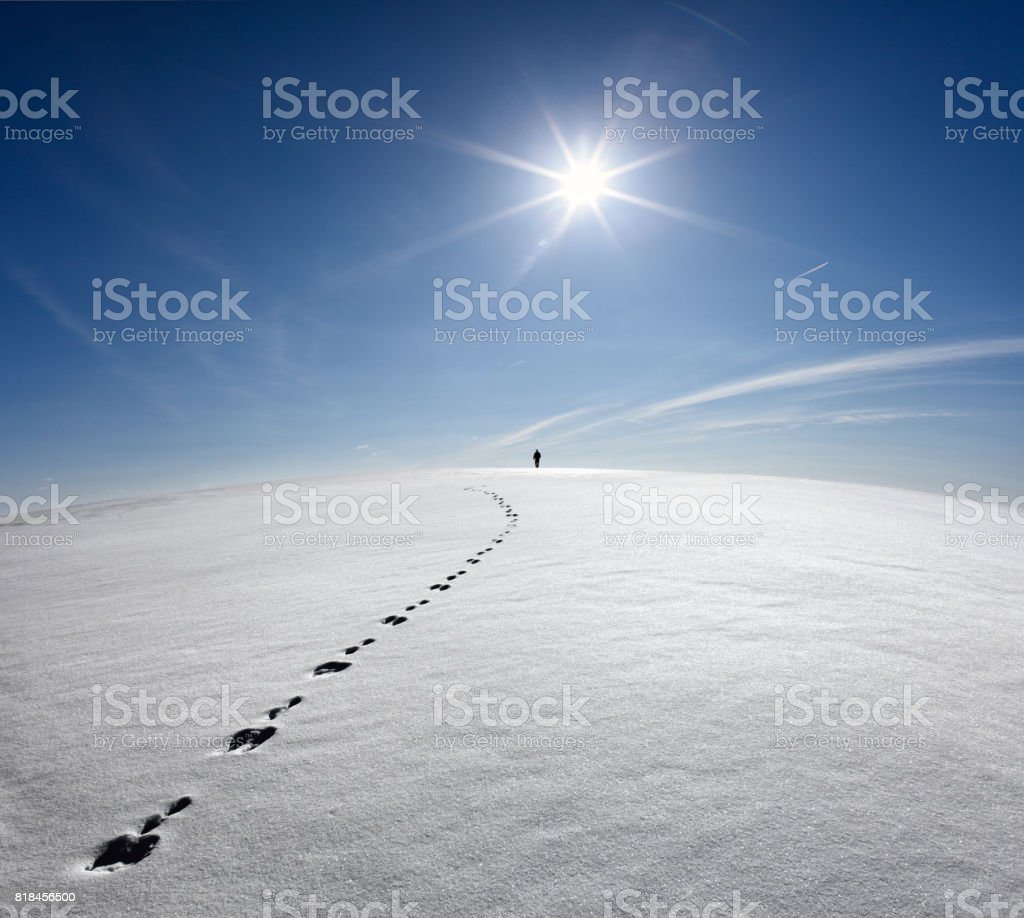 Man,Earth,Universe. Lonely Man Walking On Snow Crust Field On The Trail Of  Hare At The Background Of The Sun And Flying Plane. Abstract Photo Silhouette Of A Man On The Road In Winter Empty Field stock photo