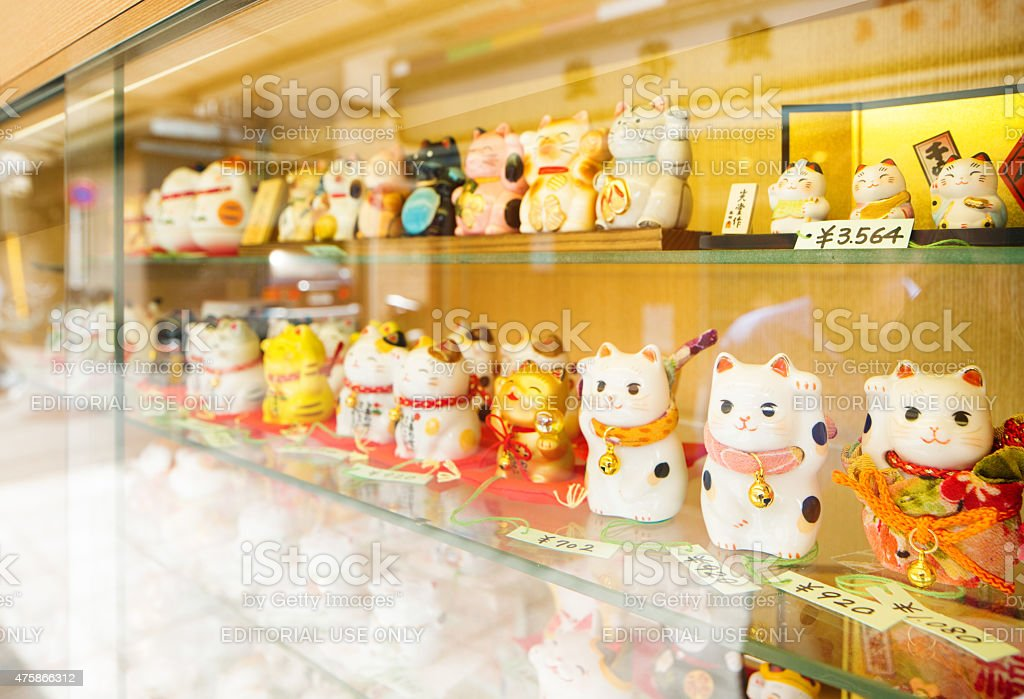 Maneki-neko lucky cat charms on display window reflection stock photo