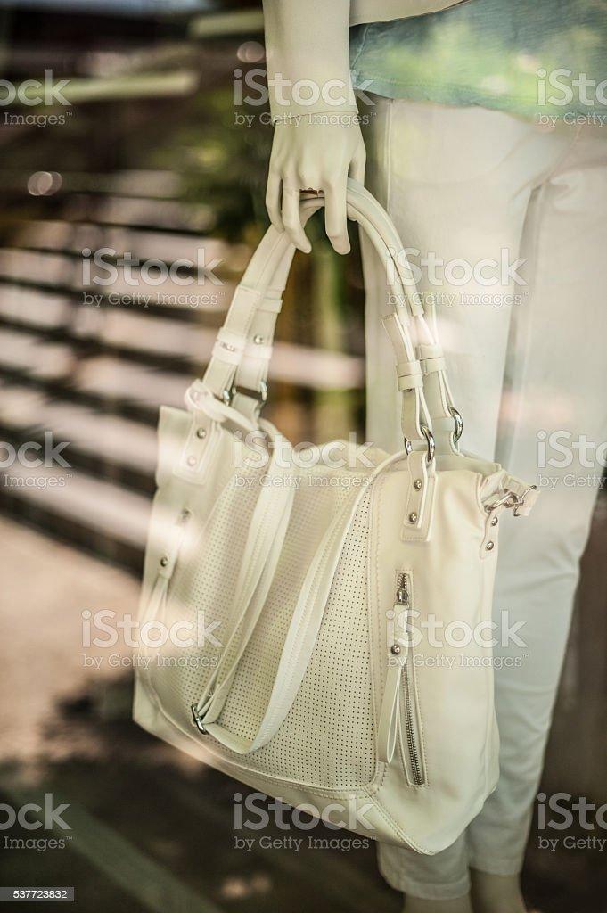 Manequin hand holding leather white handbag stock photo