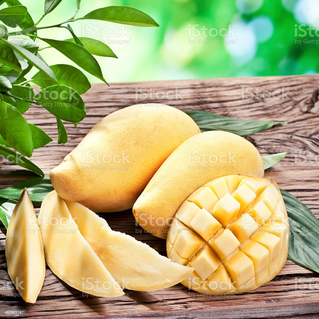 Mango fruits on a wooden table. stock photo