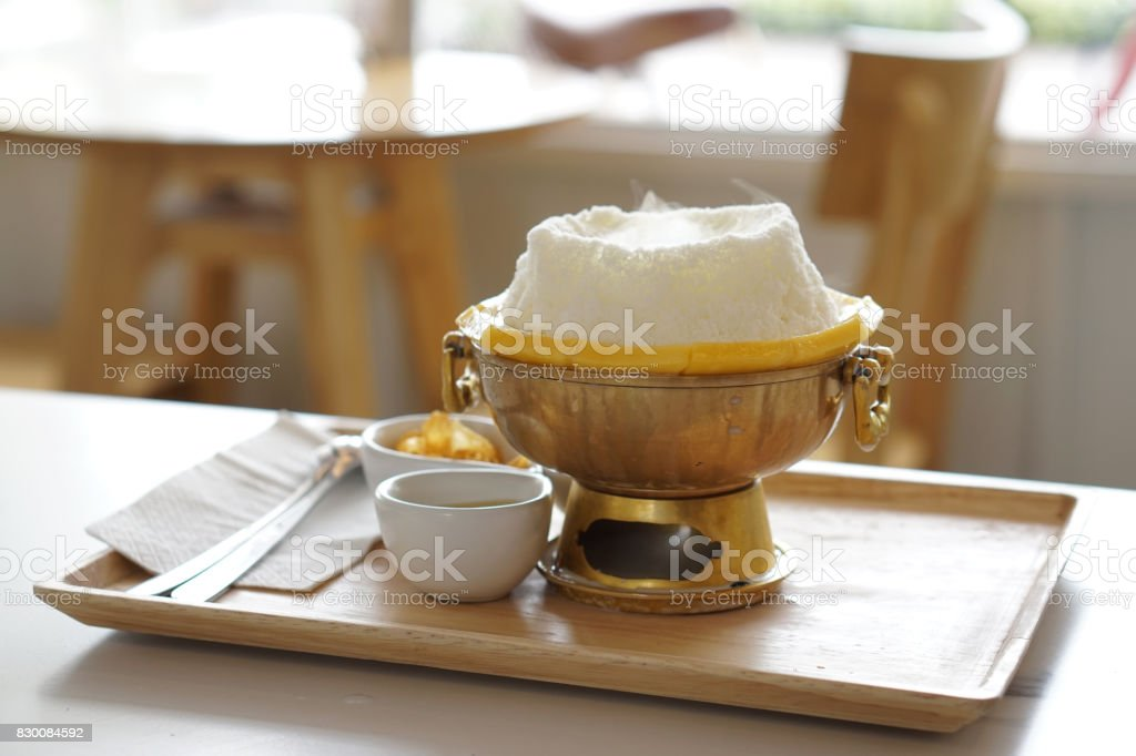 Mango shaved ice pot, also known as Bingsu and Kakigori, served in pot with corn flakes cereal, red bean and sweetened condensed milk on the table. stock photo