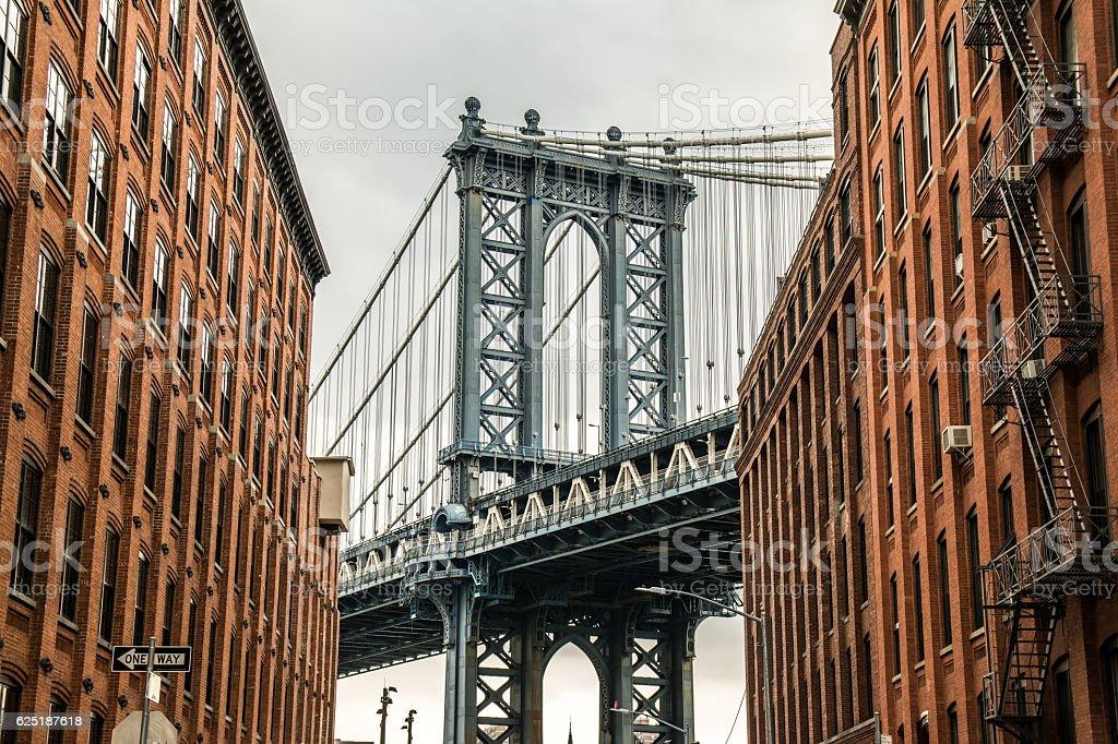 manhattan bridge between bricked facades stock photo