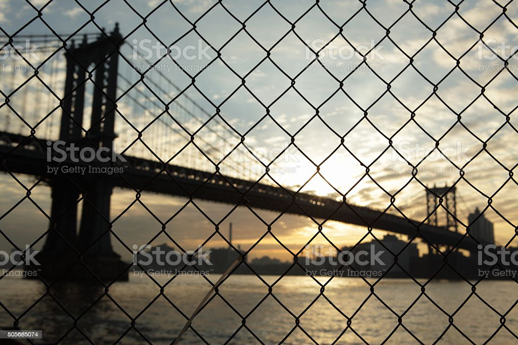 Manhattan Bridge waterfront sunrise New York through a wire fence stock photo