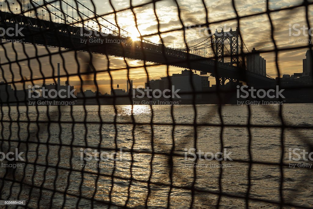 Manhattan Bridge waterfront sunrise New York through a wire fence stock photo