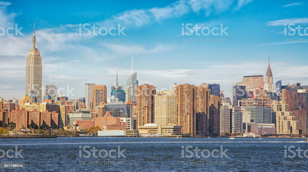 Manhattan skyline by East river against sky stock photo