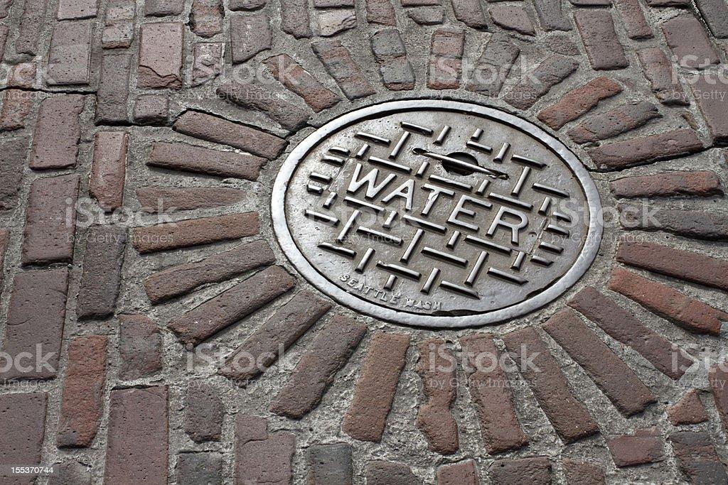 Manhole cover on a cobblestone street in Seattle Washington stock photo