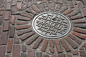 Manhole cover on a cobblestone street in Seattle Washington