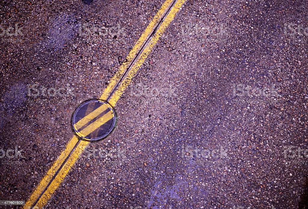 Manhole Cover with Yellow Line Askew. stock photo