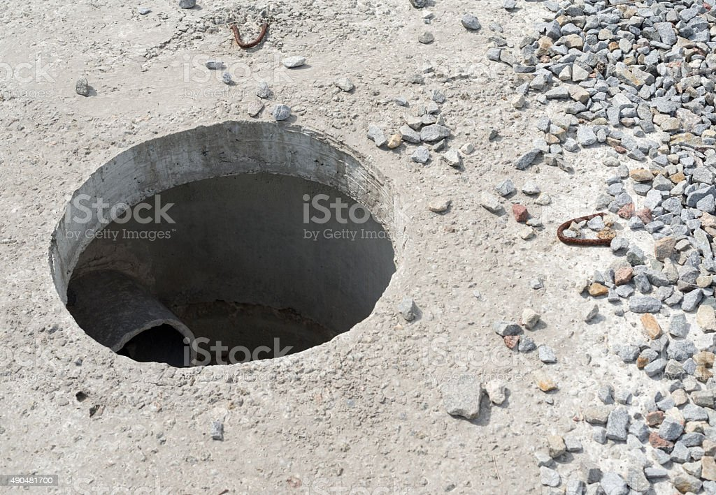 Manhole without cover in new concrete block stock photo