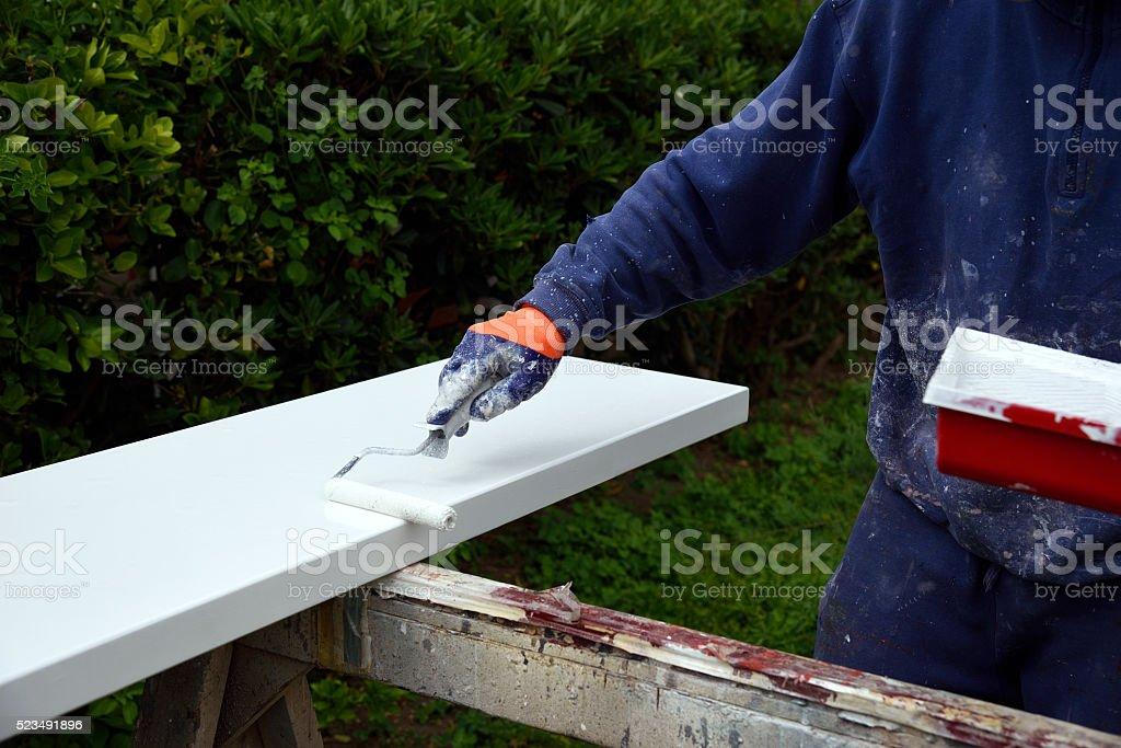 mani al lavoro con rullo e vernice stock photo