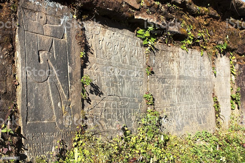 Mani wall and stones with buddhist symbols royalty-free stock photo