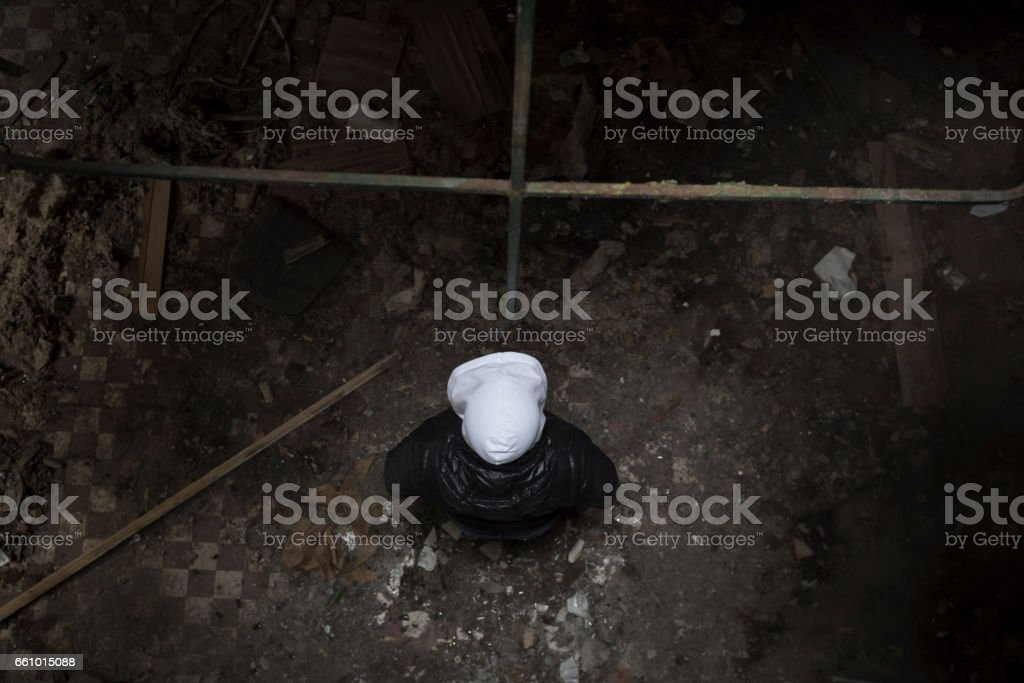 Maniac killer with hood standing in a spooky dark room. Directly above view. stock photo