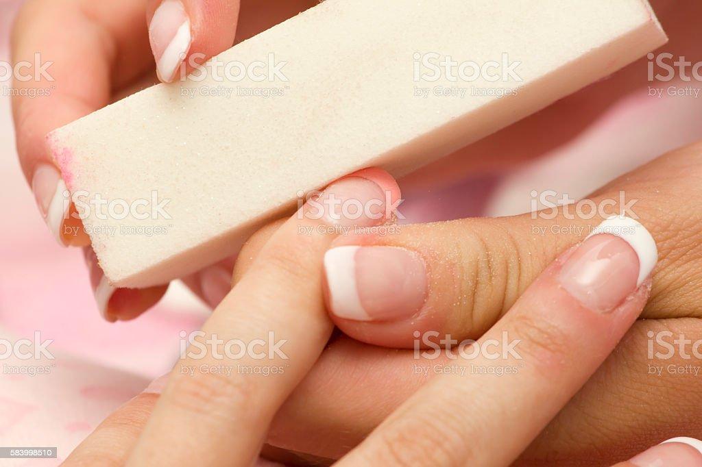 Manicure filing female fingernail with fine nail file stock photo