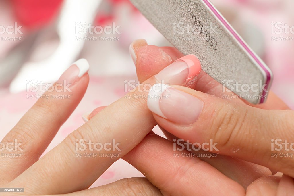 Manicure filing female fingernail with nail file stock photo