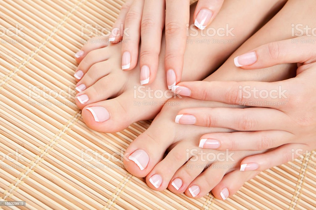 Manicure hands laying on top of manicured feet  stock photo