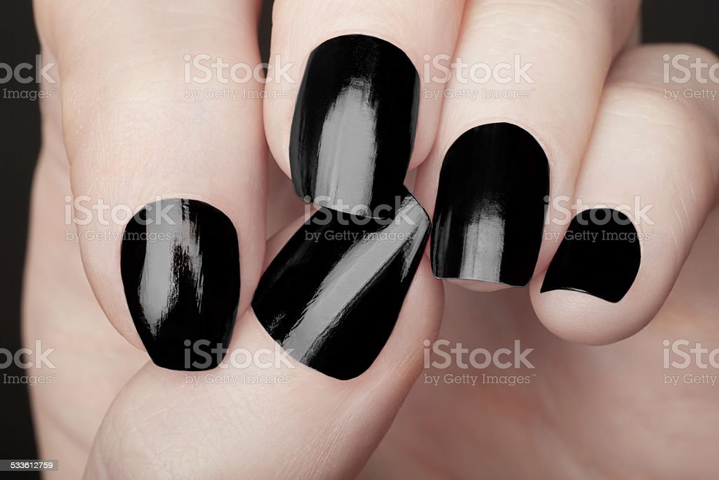 Manicure on female hands with black nail polish stock photo