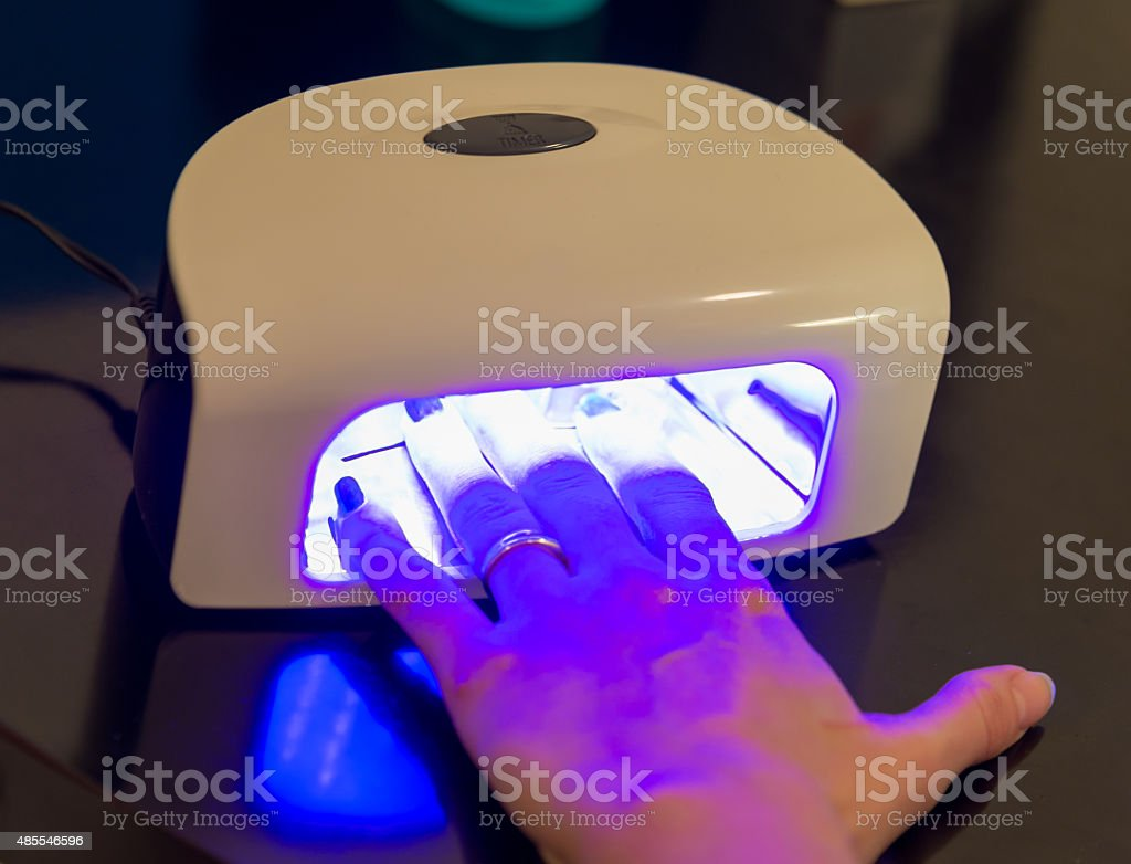 Manicure treatment under UV Nail Dryer stock photo