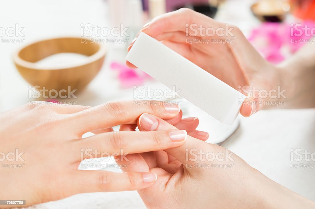 Manicure with buffer at nail salon stock photo