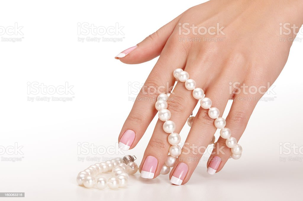 Manicured hand with white pearls draped thru fingers royalty-free stock photo