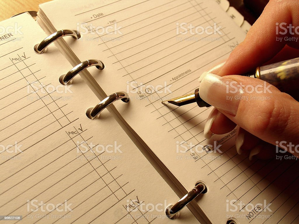 Manicured hand writing in ring bound planner royalty-free stock photo