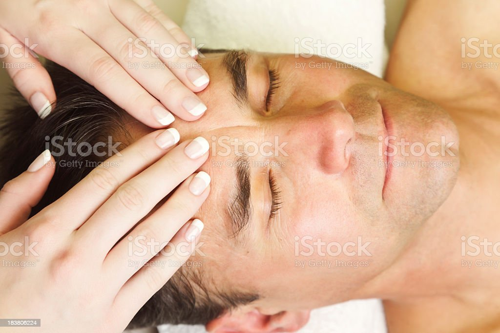 Manicured woman's hands giving a man a head massage stock photo