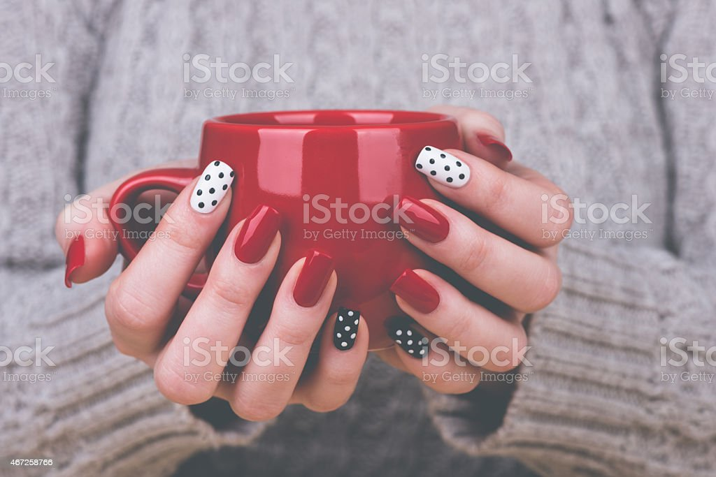 Manicured woman's hands holding cup stock photo