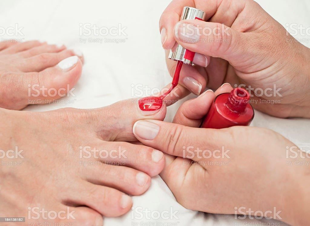 Manicurist Applying Red Nail Polish On Customer stock photo