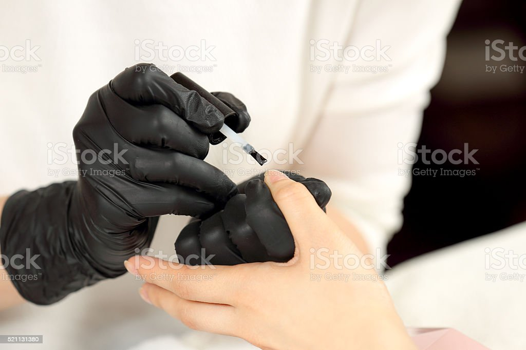 Manicurist cover colorless varnish nails client stock photo