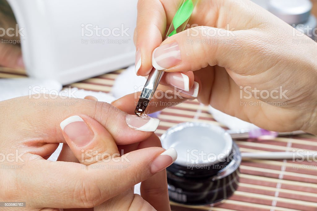 Manicurist doing white French manicure stock photo