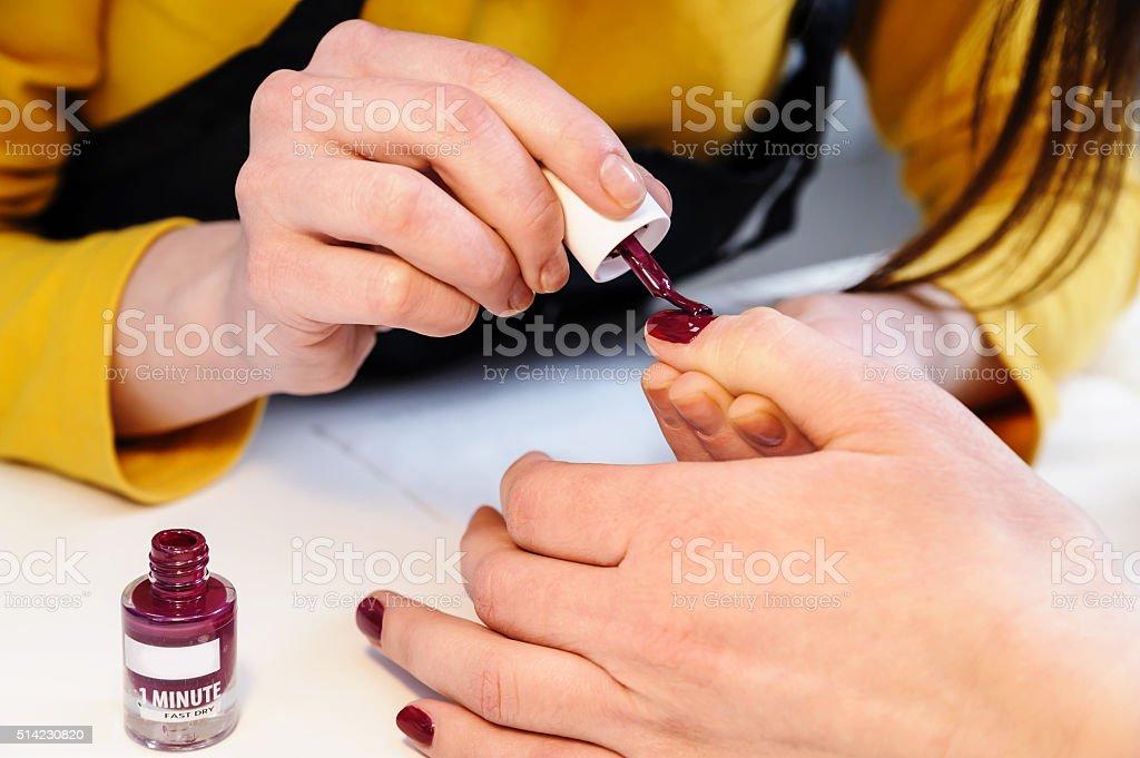 Manicurist is applying nail varnish. stock photo