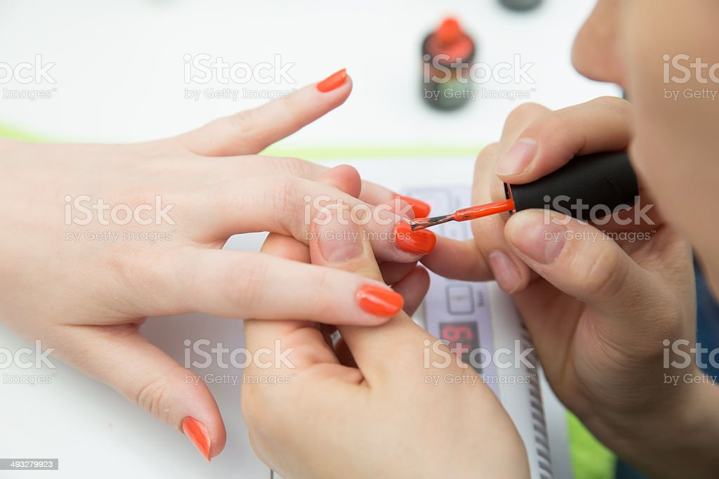 manicurists paints her nails painted orange royalty-free stock photo