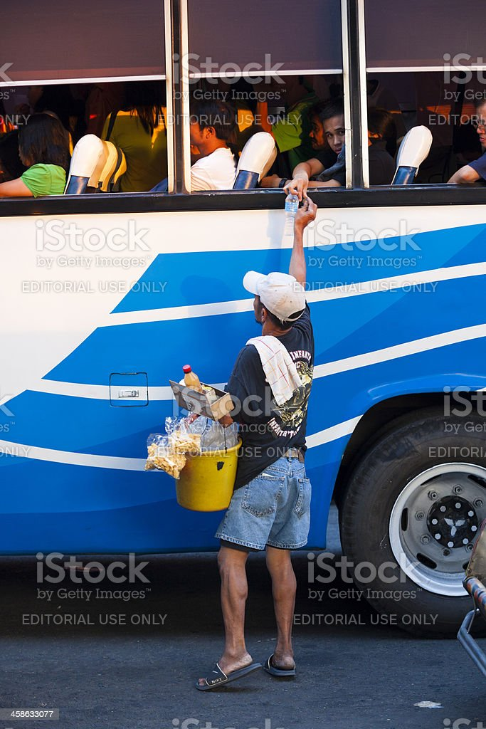 Manila, Philippines. Man sells water to a passenger stock photo