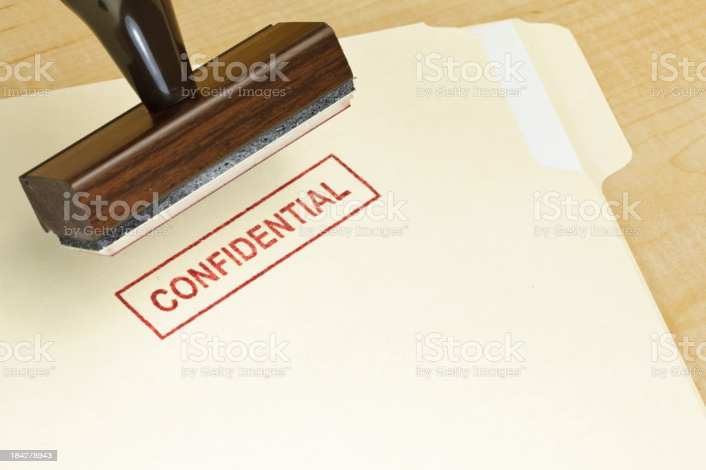 Manilla folder stamped CONFIDENTIAL with rubber stamp above royalty-free stock photo