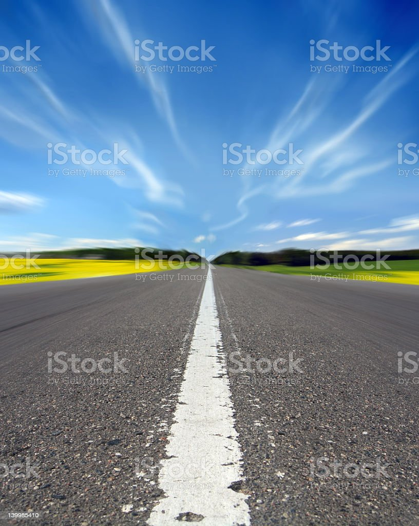 Manipulated image of a highway under a wavy blue sky royalty-free stock photo