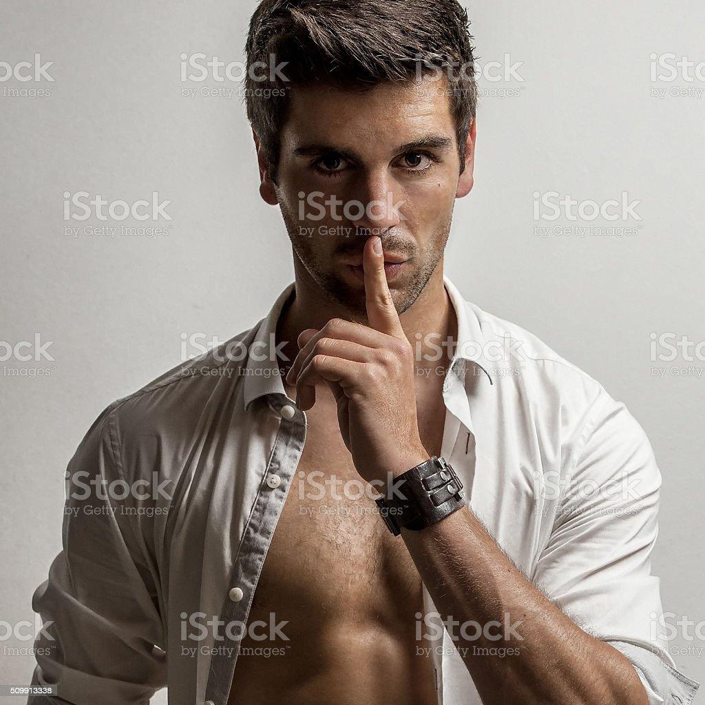 Mann mit Finger auf den Lippen und offenem Hemd stock photo