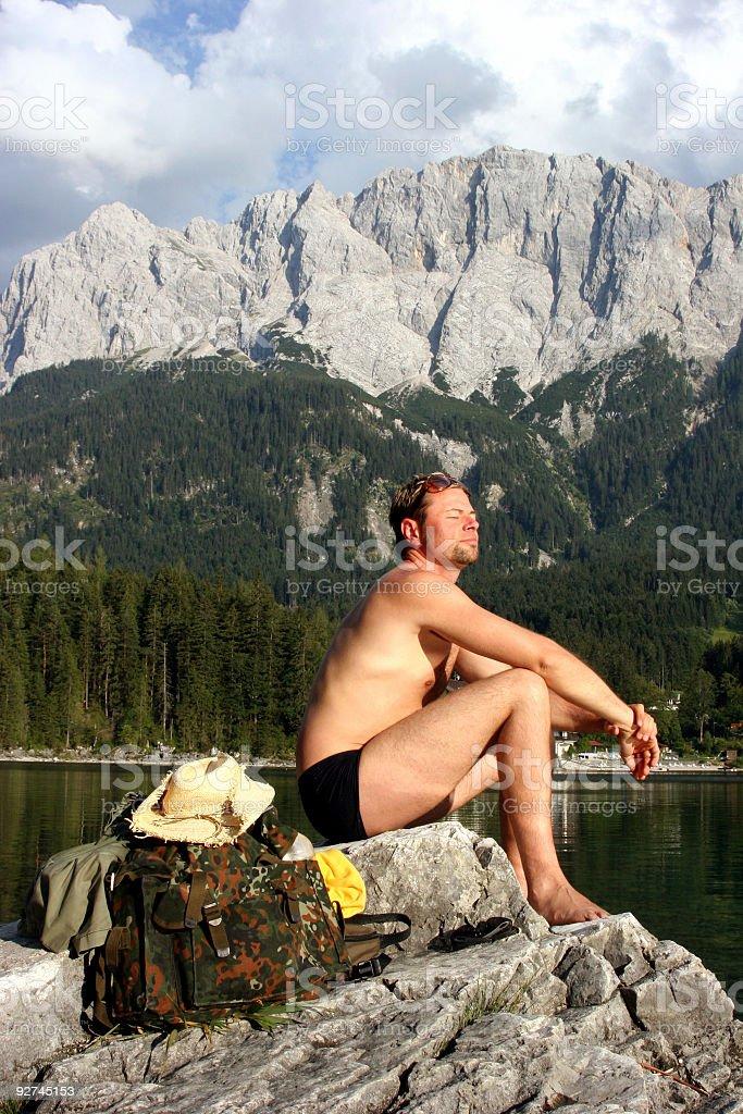 Mann sonnt sich am Eibsee mit Zugspitzmassiv stock photo