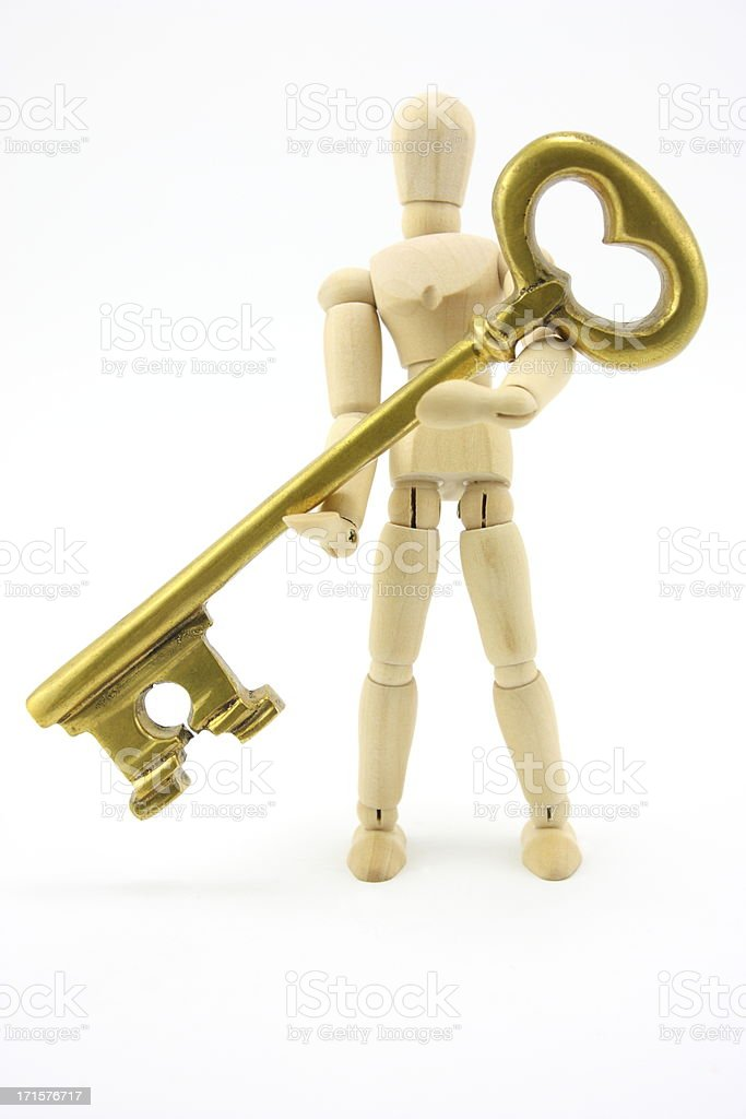 Mannequin holding gold key royalty-free stock photo