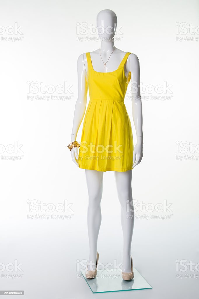 Mannequin in  yellow summer dress and  beige shoes with heels. stock photo