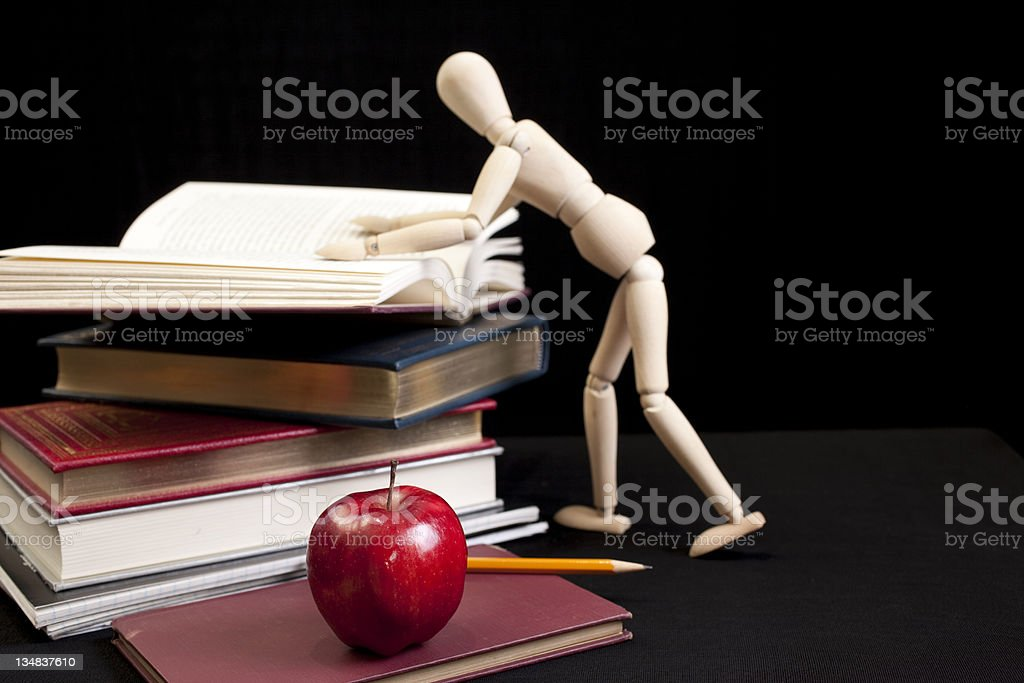 mannequin looking at stack of books with apple in foreground royalty-free stock photo