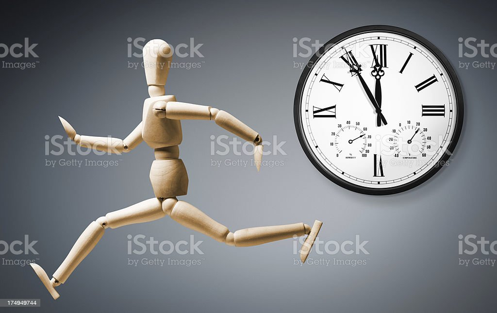 Mannequin running fast past a wall clock approaching deadline royalty-free stock photo