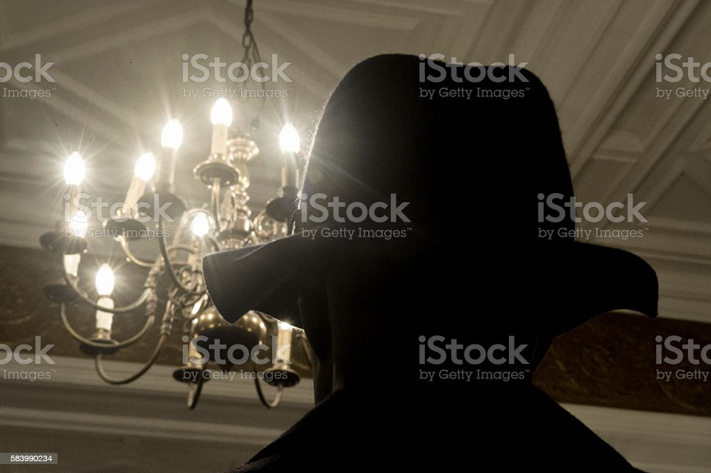 Mannequin with black hat in front of chandelier stock photo