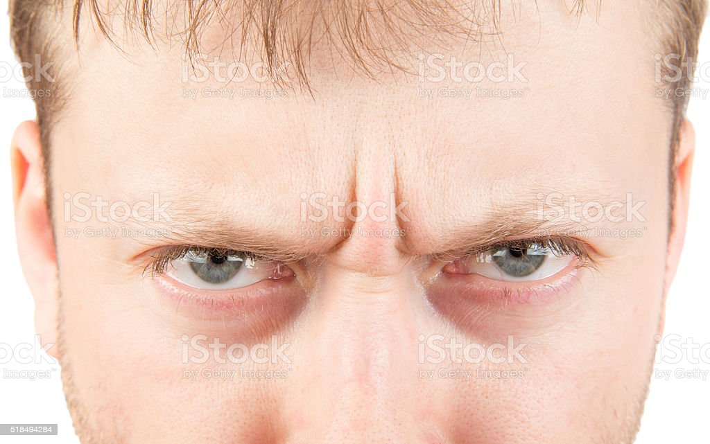 Man's angry eyes isolated on white stock photo