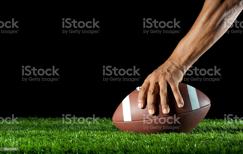 Mans arm hiking a football royalty-free stock photo