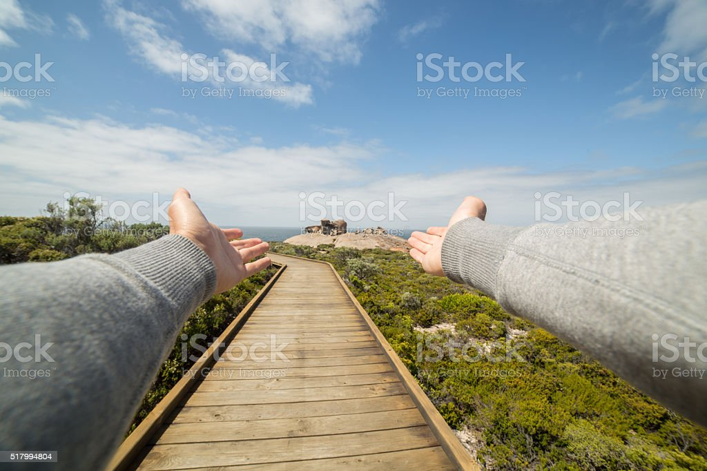Man's arms stretch towards The Remarkable rock in Kangaroo Island stock photo
